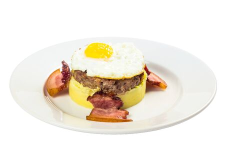 mom memade breakfast. fried egg and meat patty on top of smashed potato, decorated with bacon. food isolated on the white background. side view
