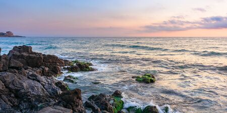 coast of the ocean at sunset. beautiful landscape with rocks in the water. gorgeous cloudscape above the horizon line. concept of calmness and mediatation Stock Photo