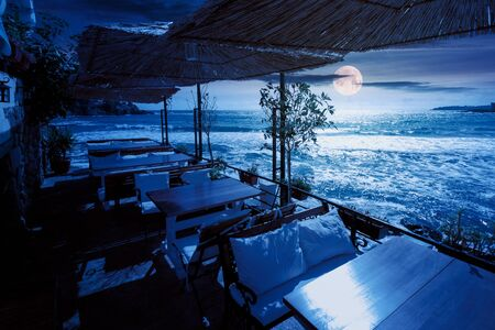 terrace of a restaurant on the sea at night. beautiful view in to the bay in full moon light. decorative umbrella above wooden tables and seats