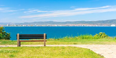 bench on the sunny beach shore. beautiful view from  paved footpath on the seaside. city and mountain in the distance beneath a blue sky with clouds Stock Photo