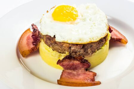 mom memade breakfast. fried egg and meat patty on top of smashed potato, decorated with bacon. food isolated on the white background. close up view
