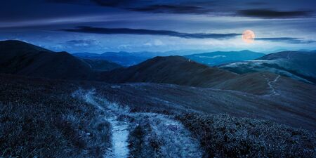 path through mountain range at night. grass on the hills and slopes. summer landscape in full moon light. panoramic view Stock Photo