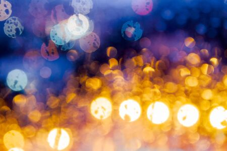 night light behind the wet window. abstract blur background