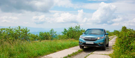 mnt. runa, ukraine - JUN 22, 2019: cyan honda cr-v suv on the mountain road. explore the wilderness concept. ridge in the distance. sunny weather. clouds on the blue sky Stock Photo - 150199728