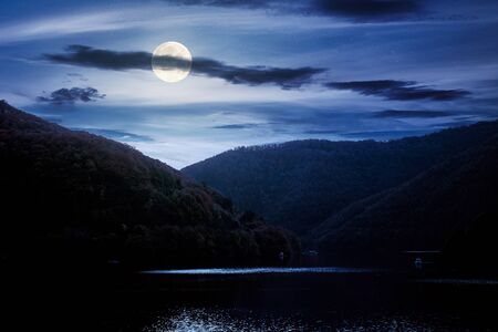 tarnita lake in romania at night. beautiful nature scenery in autumn in full moon light. gorgeous sky with glowing clouds