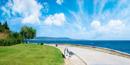 bench on the sea embankment. summer vacation and beach relax concept. nessebar beautiful travel destination of bulgaria. sunny weather. panoramic view Stock Photo