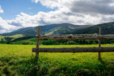 fence on the hill in rural area. early autumn scenery in carpathian mountains. sunny weather with clouds on the sky. hills rolling in tho the distant mountain ridge