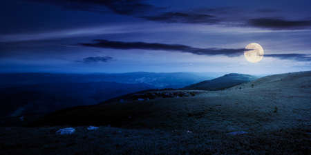 meadow with rocks on grassy alpine meadow at night. mountain scenery in summer full moon light. clouds on the blue sky above the distant ridge