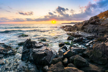 beach of the sea at sunset. wonderful scenery with stones in the water. beautiful clouds above the sun and horizon. concept of zen mood and spirituality