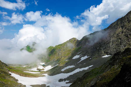 high mountain peaks among the clouds. wonderful summer landscape of fagaras ridge with some snow on hills. cloudy weather with blue sky