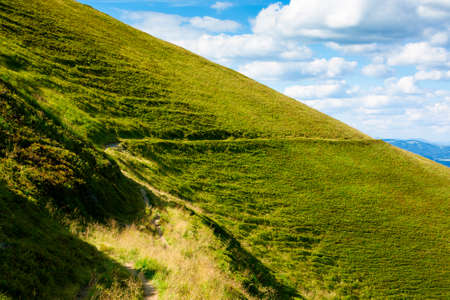 travers path through mountain range. grass on the hills and steep slopes. summer landscape on a sunny day. Stock Photo