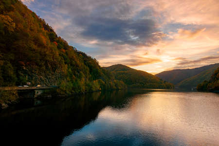 sunset on the tarnita lake in romania. beautiful nature scenery in autumn at dusk. gorgeous sky with glowing clouds
