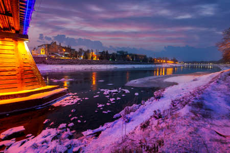 Uzhgorod, Ukraine - DEC 26, 2016: beautiful evening cityscape of old european town Uzhgorod in winter. wonderful cloudy sky over the river Uzh with some ice and snow on the shore. citylights reflect on the water surface Stock Photo - 151450826