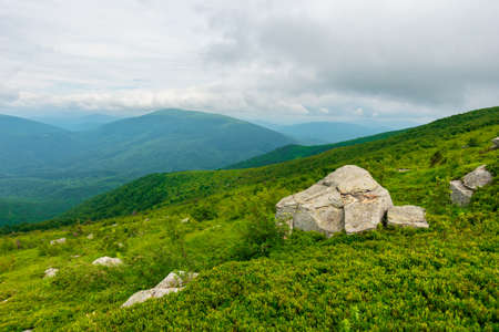 boulders on the alpine hillside. view from the edge of a hill. beautiful summer landscape in mountains. overcast windy weather  with grey clouds on the sky Stock Photo