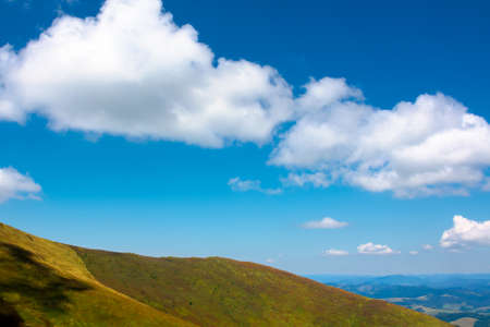 hills and meadows under the blue sky with clouds. hills and meadows under the blue sky with clouds. mountain landscape in late summer on a sunny day. beautiful scenery in august.