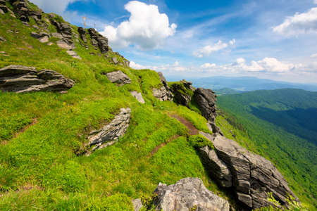 rock on the grassy slope. sunny summer landscape in mountains. ridge in the distance. clouds on the sky. challenging journey Stock Photo
