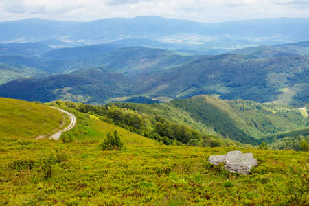 travel carpathian mountains in summer. road through green grassy meadows in the distance. idyllic landscape with clouds on the blue sky.