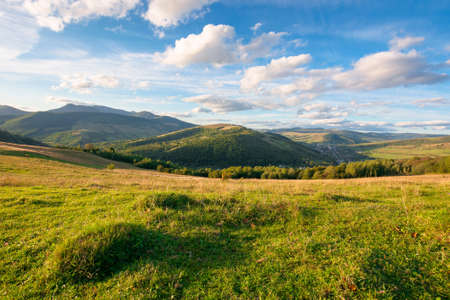 beautiful carpathian countryside. sunny afternoon. wonderful autumn landscape in mountains. rural scenery with agricultural fields on rolling hills. watershed ridge in the distance