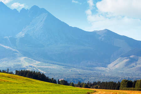 countryside summer landscape. rural fields rolling in to the distant high tatra mountain ridge in slovakia. great scenery on a sunny day Stock Photo