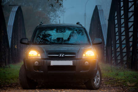 Perechin, Ukraine - OCT 20, 2019: suv headlights in foggy darkness. car on the old metal bridge with turned on light in mist environment Editorial