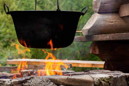traditional hungarian bogracs goulash soup. cooking dish on open fire in a cauldron. preparing healthy food outdoors concept. popular european cuisine Stock Photo