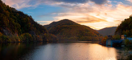 sunset panorama on the tarnita lake in romania. beautiful nature scenery in autumn at dusk. gorgeous sky with glowing clouds