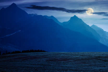 countryside summer landscape. rural fields rolling in to the distant high tatra mountain ridge in slovakia. great scenery in full moon light