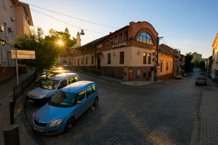 uzhhorod, ukraine - JUN 04, 2017: empty street of the old european town at sunrise. sun behind greek catholic cathedral. popular travel destination