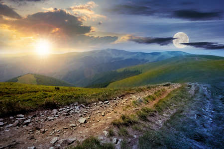 day and night time change concept above the mountain road through grassy meadow. wonderful summer adventure in twilight beneath a sky with sun and moon. Stock Photo