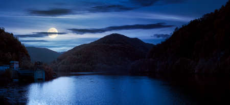 panorama of tarnita lake in romania at night. beautiful nature scenery in autumn in full moon light. gorgeous sky with glowing clouds Stock Photo