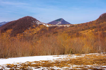 springtime in mountain landscape. leafless birch trees and snow on the meadow. ridge in the distance. sunny weather with high clouds on the blue sky