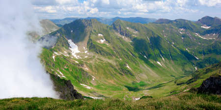 mountain scenery of romania in summertime. grass on the meadows and in the valley. rocks and snow on the steep slopes. clouds on the sky. sunny weather. fagaras ridge travel destination