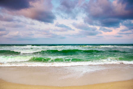 dramatic weather on the seashore. green waves crashing on the beach. cloudy purple sky in evening light
