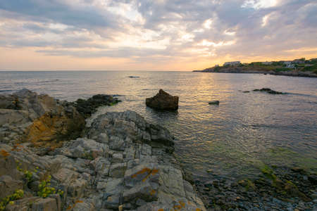 sunset at the coast of black sea. wonderful dramatic landscape with rocks on the pebble beach beneath a cloudy sky. velvet season vacations