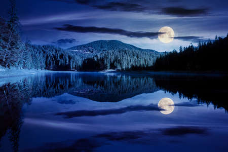 mountain lake among the forest at night. trees in colorful foliage. beautiful landscape in autumn full moon light. clouds and sky reflecting in the water Stock Photo