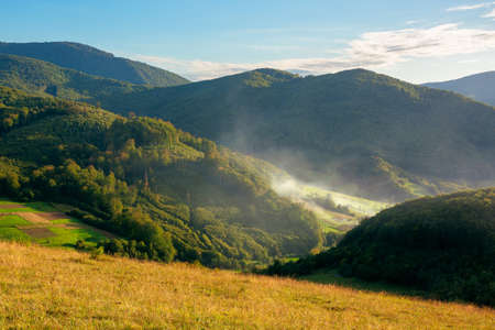 mountainous rural landscape in the evening. fields on hills among the forest. smoke or mist in the valley glowing in sunlight. clouds on the blue sky Stock Photo