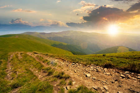 mountain road through grassy meadow at sunset. wonderful autumn adventure in evening light. clouds on the blue sky Stock Photo