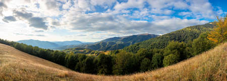 mountainous countryside in the afternoon. beautiful panorama of carpathians. valley of borzhava ridge in the distance. clouds on the sky. sunny weather Stock Photo