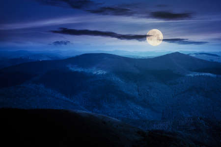 mountain landscape on a summer night. hills rolling from the valley up in to the distant ridge. view of the summer scenery in full moon light Stock Photo