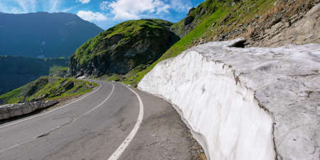 mountain road in fagaras ridge. popular travel destination. wide serpentine. summer morning scenery Stock Photo