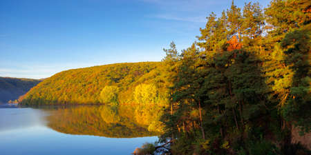 mountain lake among the forest. trees in colorful foliage. beautiful landscape on a sunny autumn morning. blue sky reflecting in the water Stock Photo - 154975133