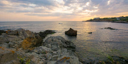 sunset at the coast of black sea. wonderful dramatic landscape with rocks on the pebble beach beneath a cloudy sky. velvet season vacations