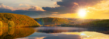 mountain lake among the forest at sunset. trees in colorful foliage. beautiful panorama in autumn evening light. clouds and sky reflecting in the water