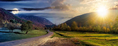day and night time change concept above country road in valley. wonderful autumn landscape in mountains with sun and moon. forest on hills in colorful foliage. dramatic sky