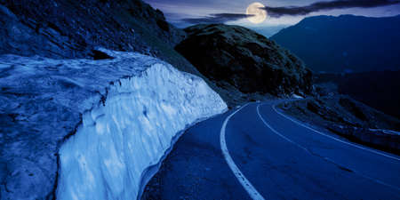 mountain road in fagaras ridge at night. popular travel destination in full moon light. wide serpentine. summer morning scenery