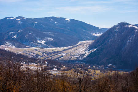mountainous countryside in early spring. dry grass and leafless trees on the hillside. snow in the distant valley and ridge