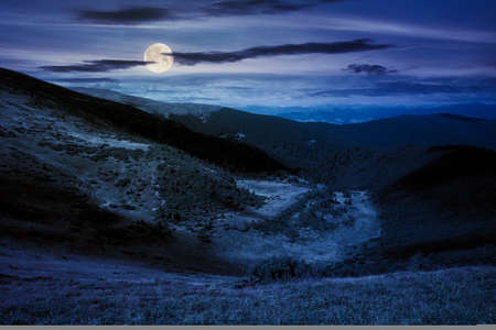 hills and valley of mountain landscape at night. clouds on the deep blue sky. beautiful scenery of chornohora ridge in full moon light Stock Photo
