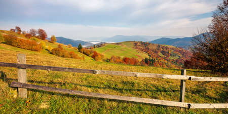 mountainous carpatian rural landscape in autumn. beautiful scenery with wooden fences on grassy rolling hills. trees in fall foliage. clouds on the sky Stock Photo
