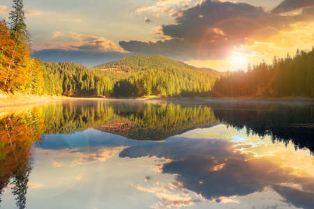 mountain lake among the forest at sunset. trees in colorful foliage. beautiful landscape in autumn evening light. clouds and sky reflecting in the water