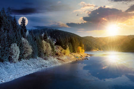 day and night time change concept above the mountain lake in autumn season. beautiful countryside scenery with sun and moon. blue sky with fluffy clouds reflecting on the water surface